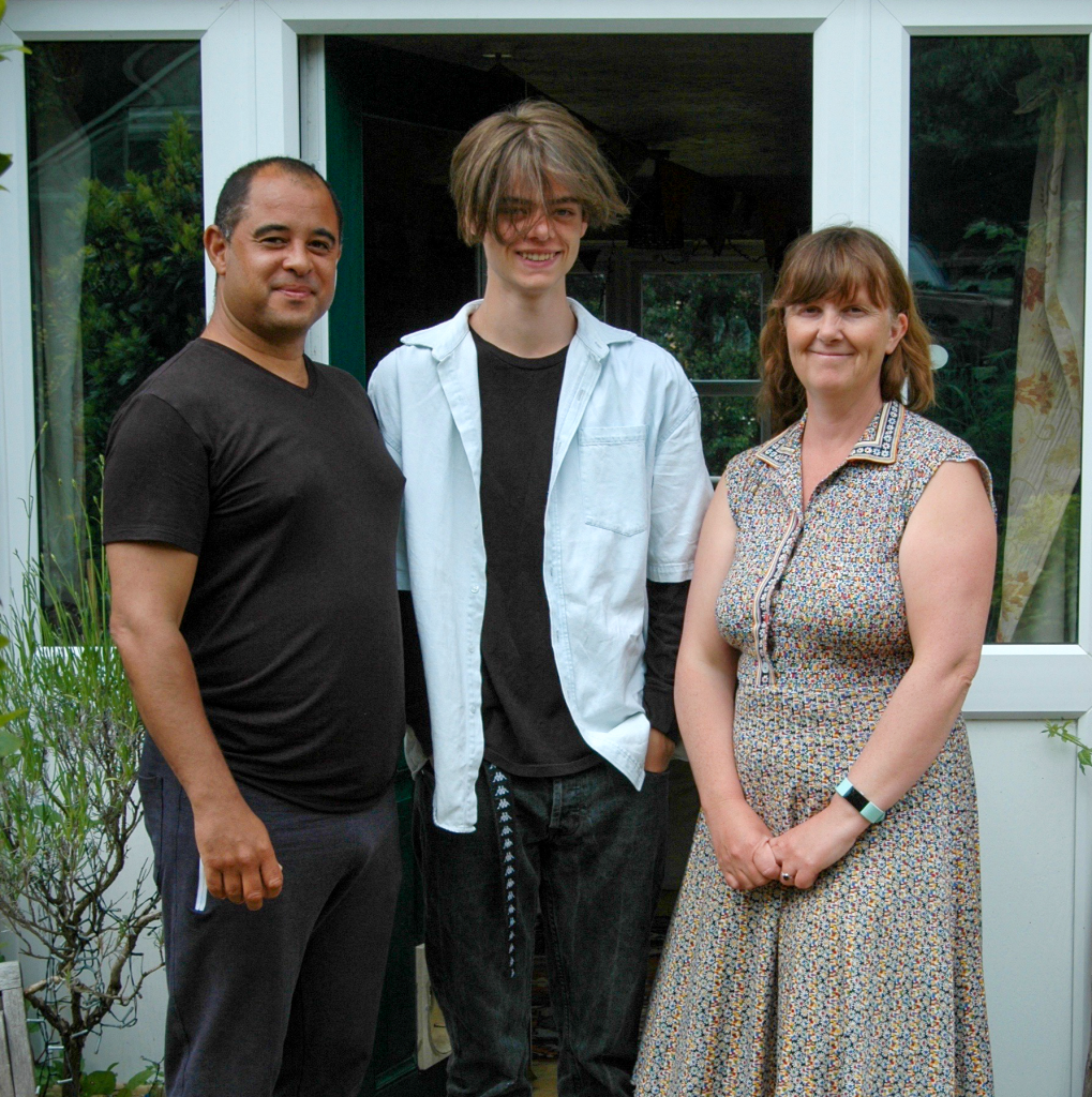 A father, son and mother in front of their house. A mixed-race family.