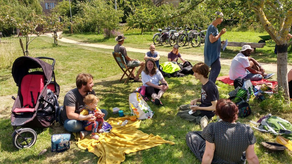 a mixed group of people of various ages and genders sharing a picnic in an orchard