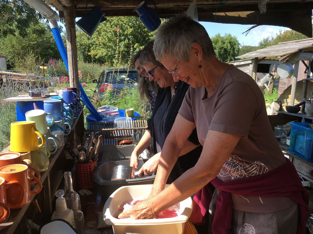 three female BC members sharing the washing up at an outside kitchen